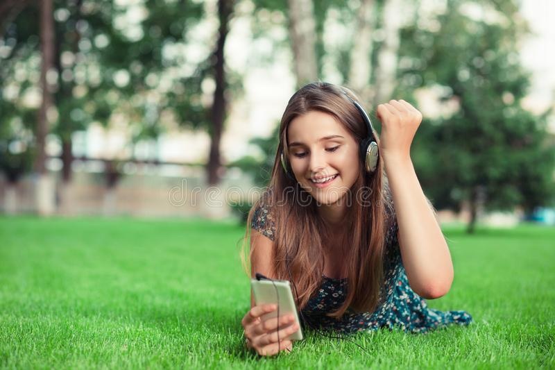 Mujer que anima en las buenas noticias en su tel?fono m?vil y que perfora el aire con su pu?o fotos de archivo