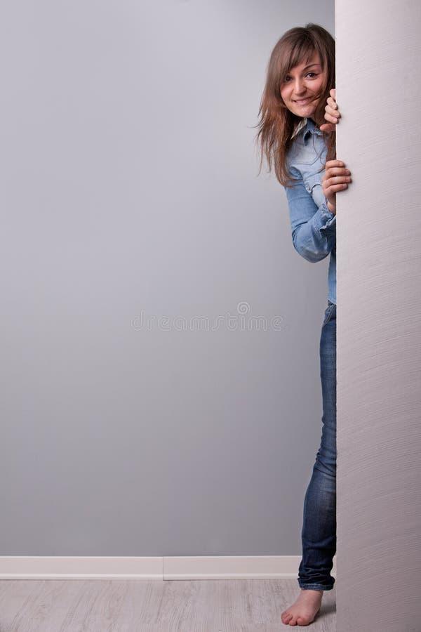 Mujer que aparece detrás de la pared fotografía de archivo libre de regalías