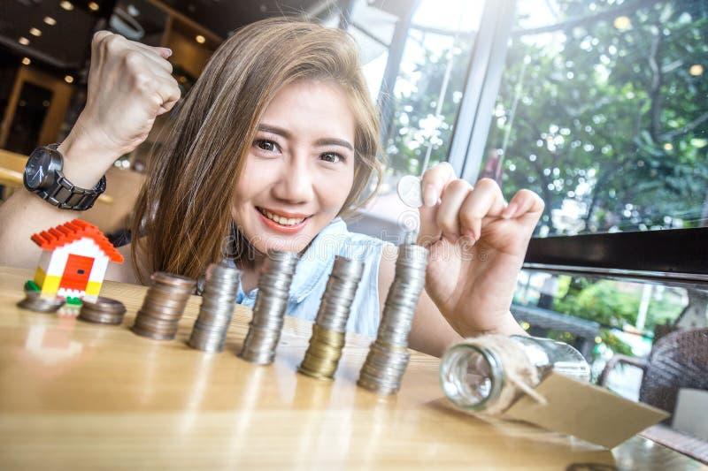 Mujer que apila monedas de oro en columnas con modo de la casa foto de archivo libre de regalías