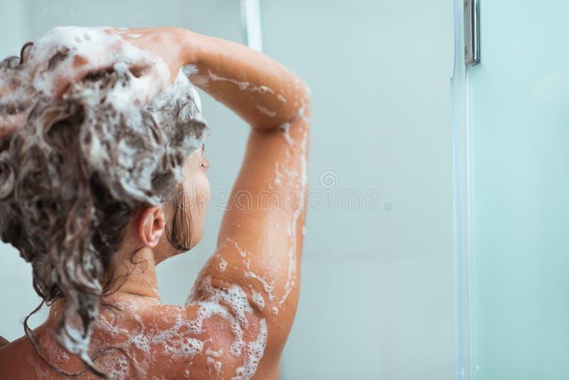 Mujer que aplica champú en ducha imágenes de archivo libres de regalías