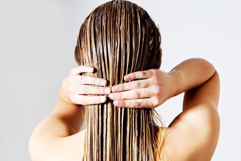 Mujer que aplica el acondicionador de pelo Aislado en blanco foto de archivo