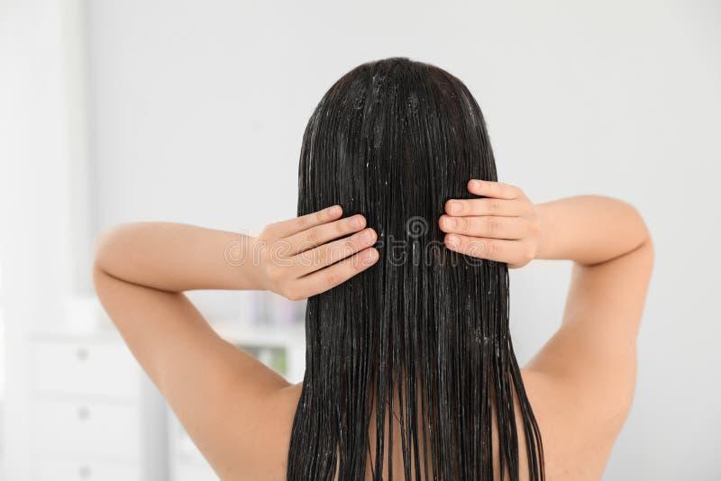 Mujer que aplica el acondicionador de pelo en cuarto de baño imagen de archivo