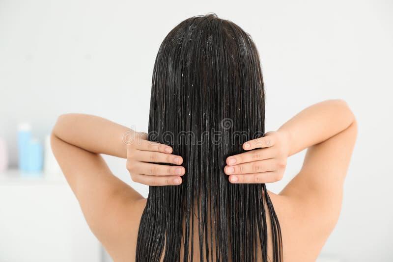 Mujer que aplica el acondicionador de pelo fotografía de archivo libre de regalías