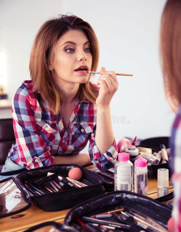 Mujer que aplica el lápiz labial imagenes de archivo