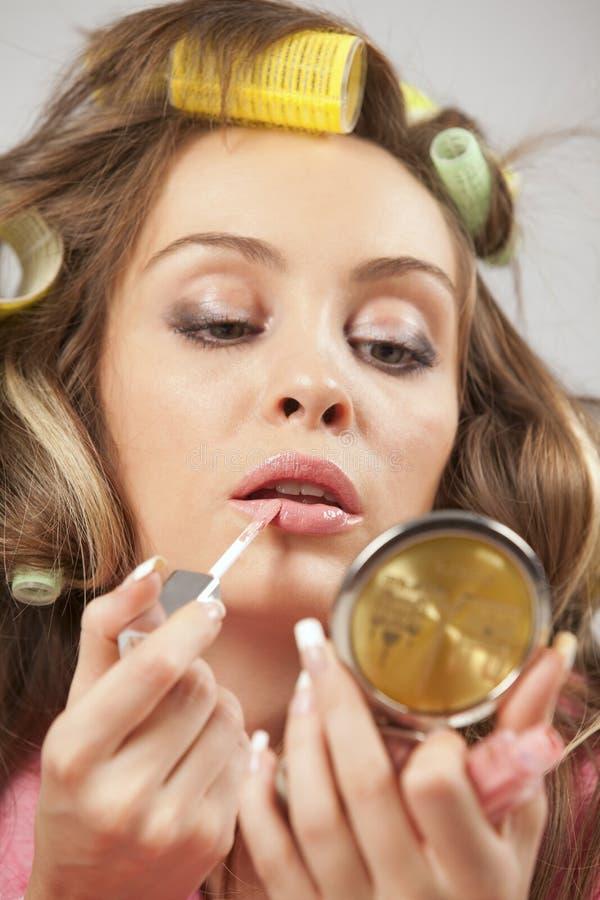 Mujer que aplica el lápiz labial brillante líquido imagenes de archivo