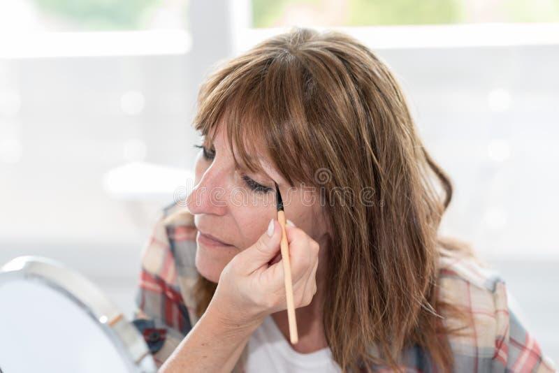 Mujer que aplica el polvo del sombreador de ojos fotografía de archivo