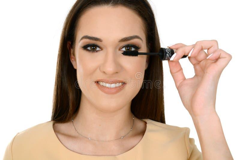 Mujer que aplica el rimel negro en las pestañas con el cepillo del maquillaje fotos de archivo