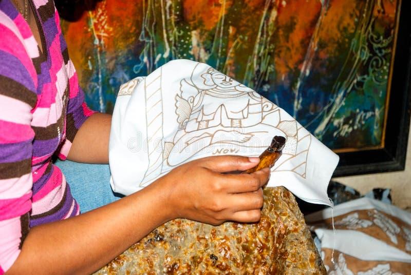 Mujer que aplica la cera en el batik imagen de archivo