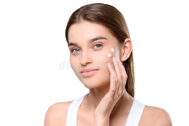 Mujer que aplica la crema de cara imágenes de archivo libres de regalías