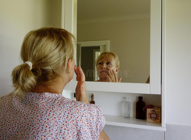 Mujer que aplica la crema de cara foto de archivo libre de regalías