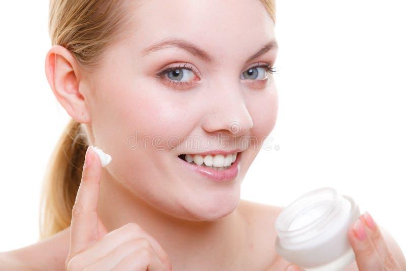 Mujer que aplica la crema de cara con su finger fotos de archivo