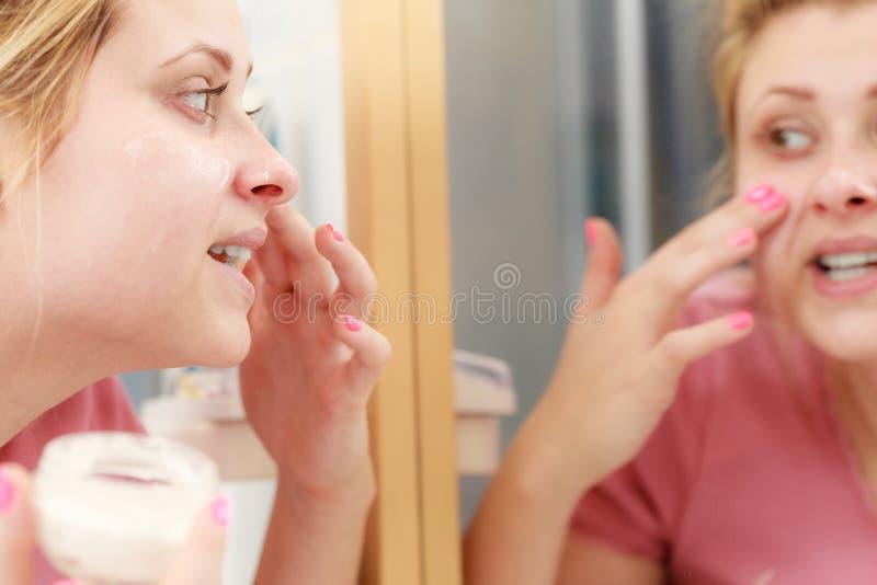 Mujer que aplica la crema de cara con su finger imagen de archivo
