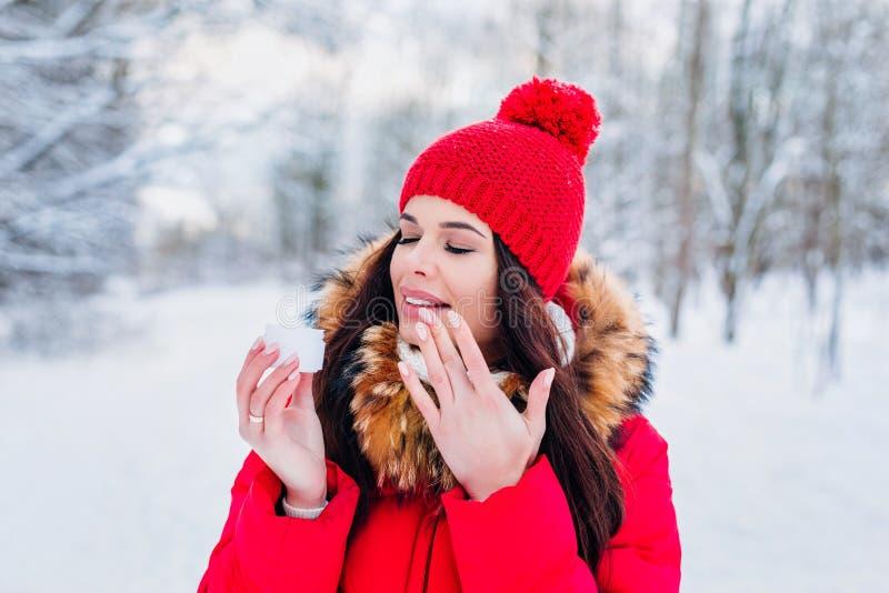 Mujer que aplica la crema de la crema hidratante para hidratar la piel en invierno imagenes de archivo