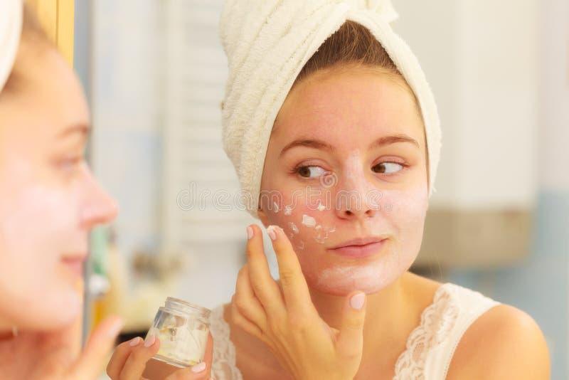 Mujer que aplica la crema de la máscara en cara en cuarto de baño imágenes de archivo libres de regalías