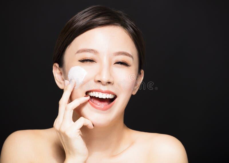 Mujer que aplica la crema de la loción en cara fotografía de archivo libre de regalías