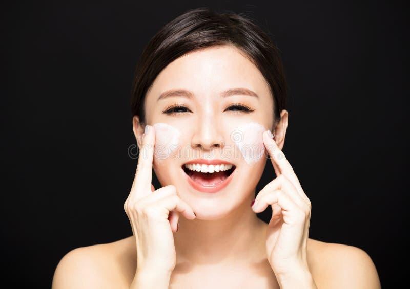 Mujer que aplica la crema de la loción en cara fotografía de archivo