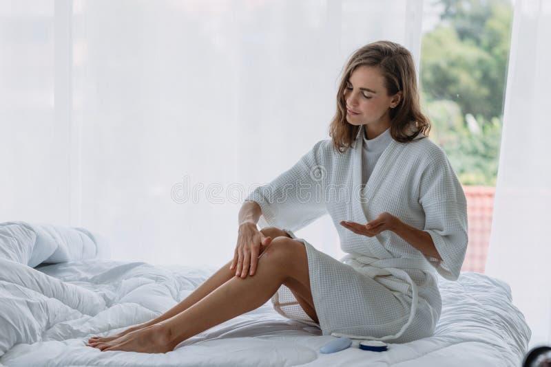 Mujer que aplica la crema de la loci?n en sus piernas en la cama en dormitorio foto de archivo libre de regalías