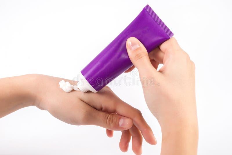 Mujer que aplica la crema de la mano en la palma de la belleza del tubo púrpura imagen de archivo libre de regalías