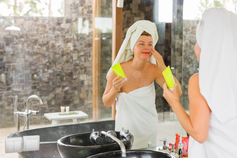 Mujer que aplica la crema de piel en cara imagenes de archivo