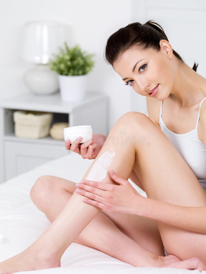 Mujer que aplica la crema en su pierna foto de archivo libre de regalías