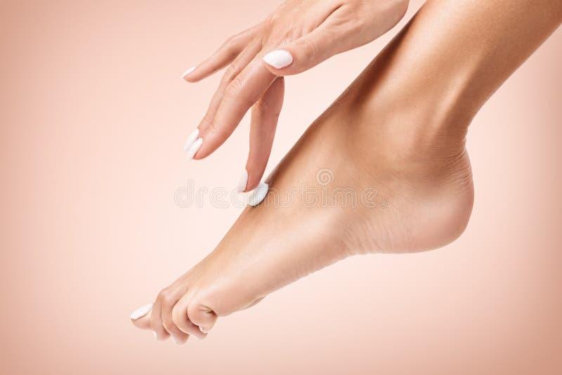 Mujer que aplica la crema en sus pies hermosos imágenes de archivo libres de regalías