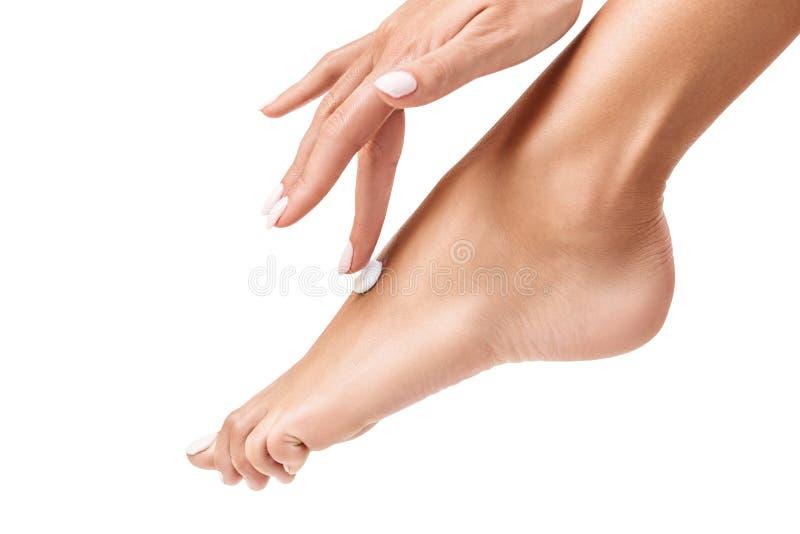 Mujer que aplica la crema en sus pies hermosos imagenes de archivo