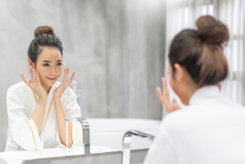 Mujer que aplica la espuma para lavarse en su cara y mirar el espejo imagen de archivo libre de regalías