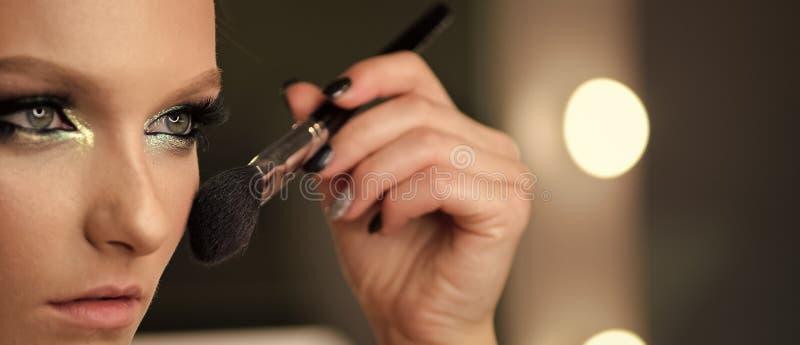Mujer que aplica la fundación tonal cosmética seca en cara usando cepillo del maquillaje fotos de archivo libres de regalías