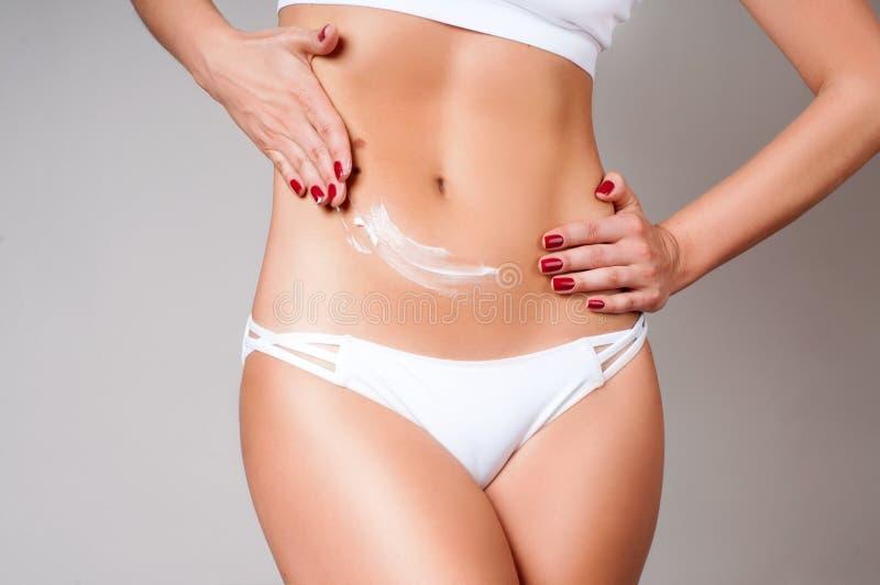 Mujer que aplica la loción poner crema de la crema hidratante en el vientre Ropa interior del blanco del desgaste de mujer fotos de archivo