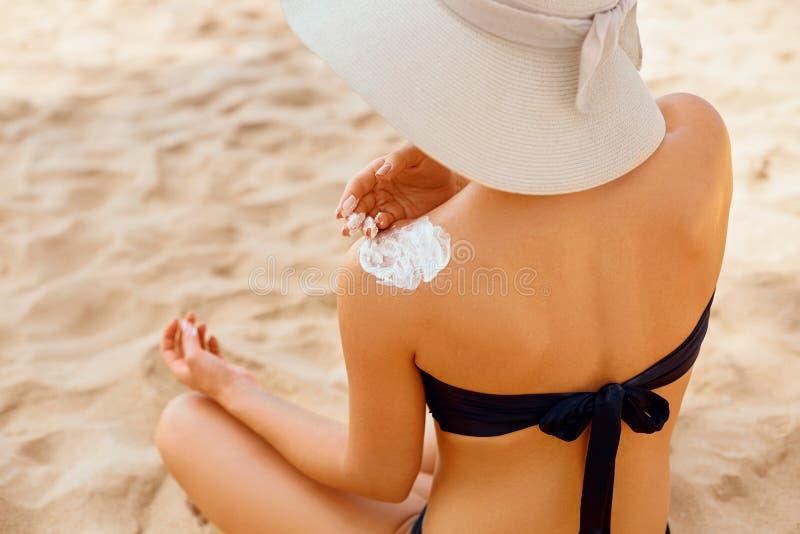 Mujer que aplica la nata de la protecci?n solar en hombro bronceado Cuidado de piel Crema del sol de la protecci?n de Sun del cue foto de archivo