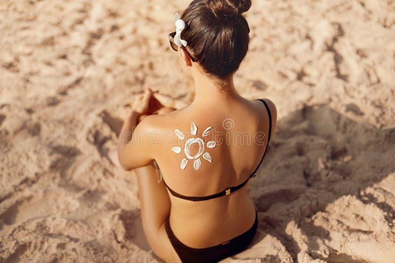 Mujer que aplica la nata poner crema de Sun en hombro bronceado en la forma de The Sun Protecci?n de Sun foto de archivo
