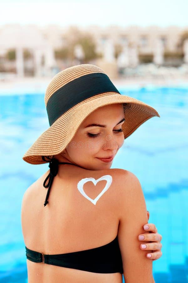 Mujer que aplica la nata poner crema de Sun en hombro bronceado Protecci?n de Sun Crema de Sun Cuidado de la piel y del cuerpo fotos de archivo