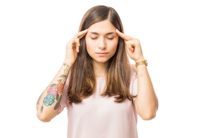 Mujer que aplica la presión apacible sobre el templo de su cabeza imágenes de archivo libres de regalías