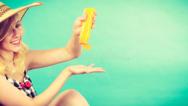 Mujer que aplica la protección solar en la mano fotografía de archivo