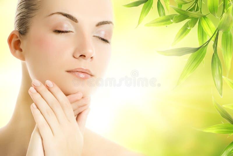 Mujer que aplica los cosméticos orgánicos a su piel imagenes de archivo