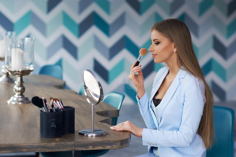 Mujer que aplica maquillaje imagenes de archivo