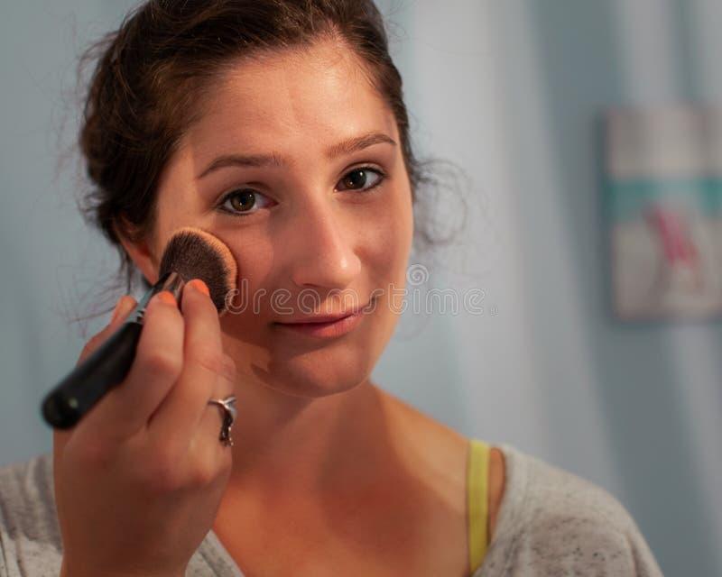 Mujer que aplica maquillaje imagen de archivo libre de regalías