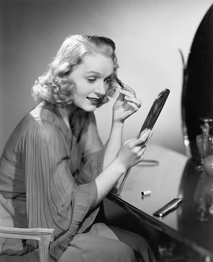 Mujer que aplica maquillaje (todas las personas representadas no son vivas más largo y ningún estado existe Garantías del proveed foto de archivo