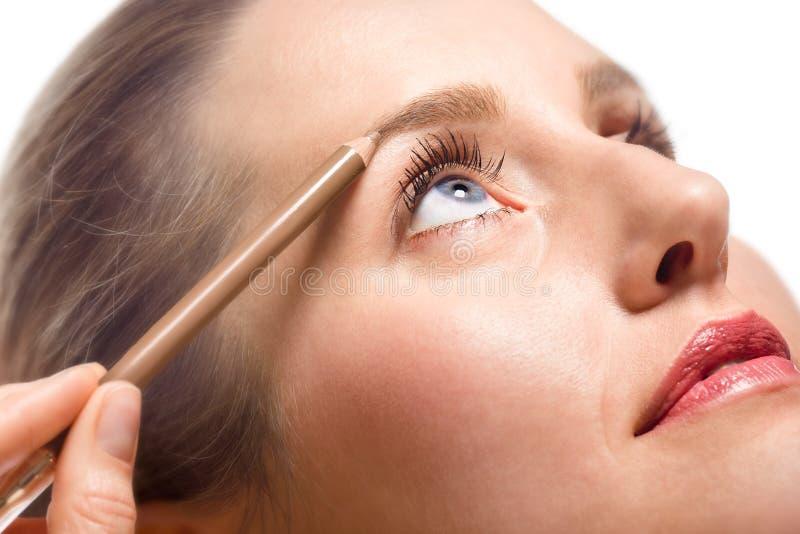 Mujer que aplica maquillaje usando el lápiz de ceja imagen de archivo libre de regalías