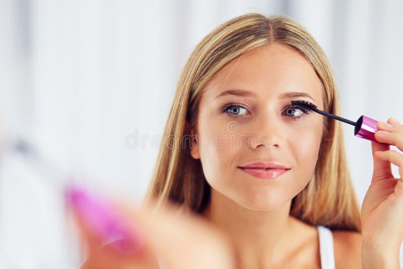 Mujer que aplica maquillaje y que mira en el espejo Pestañas de pintura con rimel fotos de archivo libres de regalías