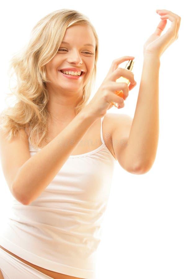 Mujer que aplica perfume en la muñeca imágenes de archivo libres de regalías