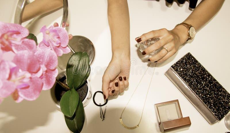 Mujer que aplica perfume en su muñeca imagenes de archivo