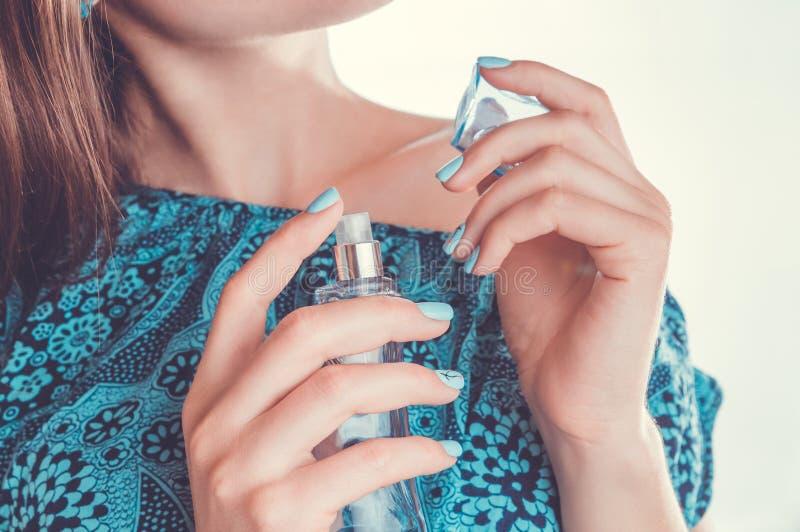 Mujer que aplica perfume en su muñeca fotos de archivo