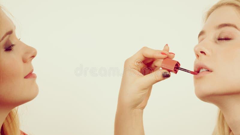 Mujer que aplica su l?piz labial del amigo en los labios fotos de archivo libres de regalías