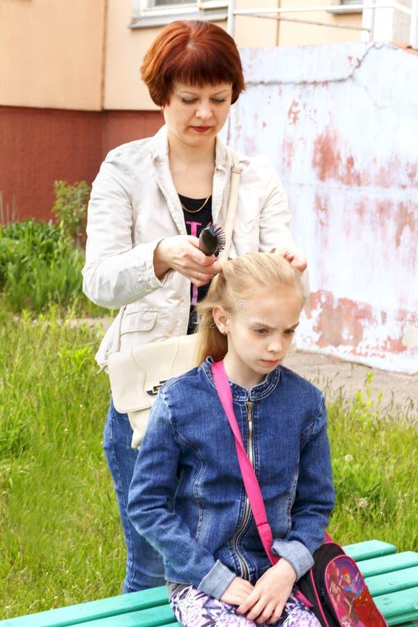 Mujer que aplica su pelo de la hija con brocha fotos de archivo libres de regalías