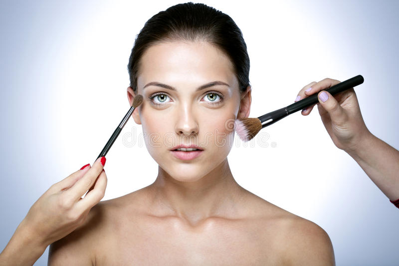 mujer que aplica tonal cosmético seco foto de archivo libre de regalías