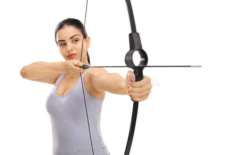 Mujer que apunta con un arco y una flecha fotografía de archivo