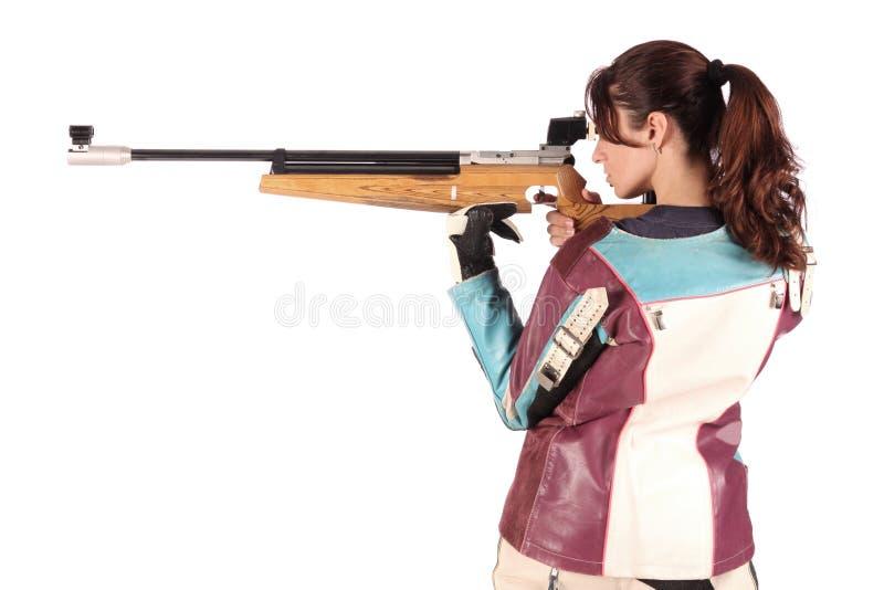 Mujer que apunta un rifle de aire neumático foto de archivo