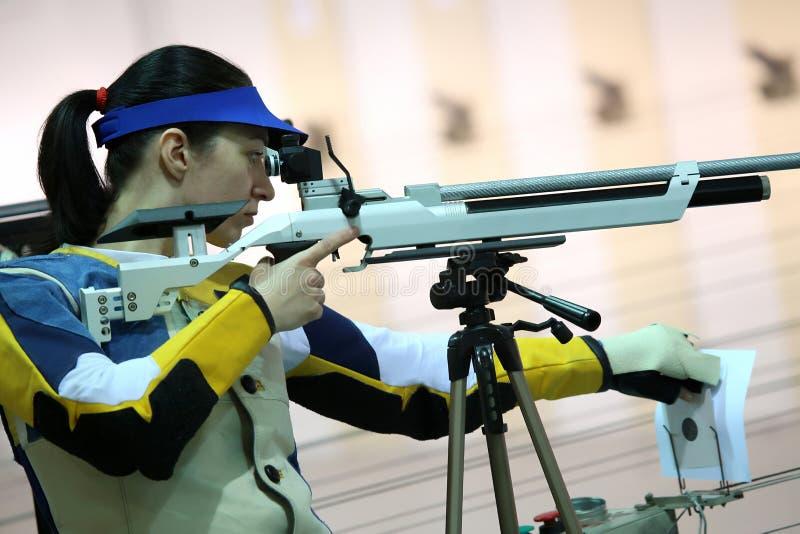 Mujer que apunta un rifle de aire neumático foto de archivo libre de regalías