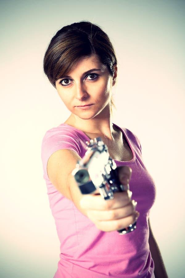 Mujer que apunta una arma de mano fotografía de archivo libre de regalías